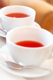 Two cups of tea. Elegant white cup of tea on a table in a restaurant. Table covered with beige cloth. On the table dishes: plates with dessert, sugar, metal Royalty Free Stock Photos