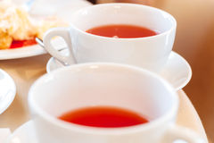 Two cups of tea. Elegant white cup of tea on a table in a restaurant. Table covered with beige cloth. On the table dishes: plates with dessert, metal devices Stock Photography