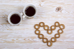 Two cups for tea with fragrant bagels on  wooden background Royalty Free Stock Images