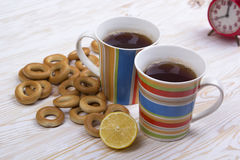 Two cups for tea with fragrant bagels on  wooden background Royalty Free Stock Photo