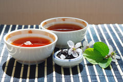 Two cups of tea, jar of tea leaves Royalty Free Stock Photos