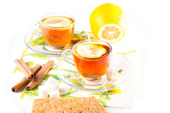 Two cups of tea. With lemon and cinnamon on transparent saucers Royalty Free Stock Images