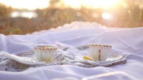 Two cups of tea with lemon at sunset. Delicious hot tea on a white table cloth on a background of an autumn sunset with glare stock footage