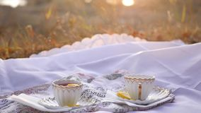 Two cups of tea with lemon at sunset . Two cups of delicious tea on the saucer on a tablecloth stock footage