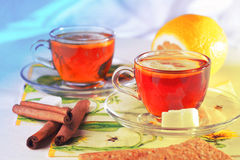 Two cups of tea. With lemon on transparent saucer near cinnamon sticks Royalty Free Stock Photos