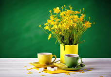 Two cups with tea and lemon are on the wooden table. Vase with yellow buttercups on a green background. Stock Photo