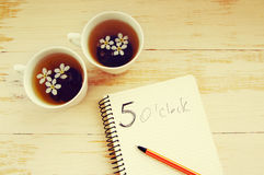 Two cups of tea with spring flowers and notebook. With an inscription of 5 hours (tea drinking time) on a wooden background Stock Image