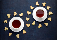 Two cups of tea and weave of cookie in shape of heart on blue stone background. Stock Images