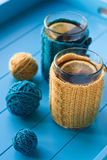 Two cups of tea in yellow Knitted sweaters on  background Royalty Free Stock Photos