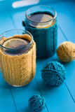 Two cups of tea in yellow Knitted sweaters on background Stock Photo