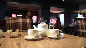Two cups and teapot at cafe table. Blurred people background. Cafe interior 4k. Two cups and teapot at cafe table. Blurred people background. Cafeteria interior stock video