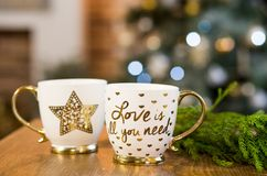 Two cups with text in Christmas interior with lights on background stock images