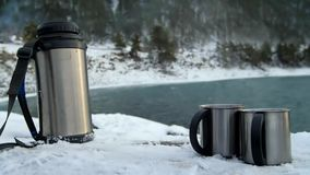 Two Cups With Thermos in Snowy Winter. Pouring tea from a thermos. Two Cups With Thermos in Snowy Winter. Slow motion stock footage