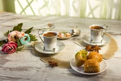 Two cups of Turkish coffee and a plate with baklava. Two cups of Turkish coffee and glasses of water and a plate with baklava lukum in lukumluk decorative Stock Images