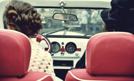 Two curly girl in medieval dress in vintage cars. Vintage style. Royalty Free Stock Photos