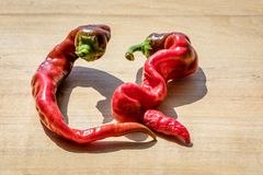 Curvy cayenne peppers on a wooden block next to each other. Two curvy cayenne peppers on a wooden block next to each other stock photo