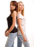 Two curvy young woman standing back. Two attractive curvy young women in casual jeans and summer tops standing back to back sideways to the camera, studio royalty free stock images