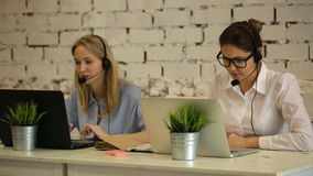 Two customer service representatives at work. Two cheerful young female customer service representatives in headset working at the computer and smiling stock footage