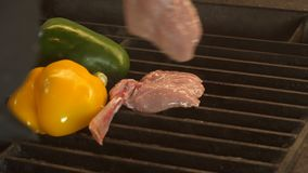 Two cut halves of green pepper are grilled, the chef in black gloves lays meat on a bone on the grill next to peppers. Lamb or veal on the bone, grilled stock video footage