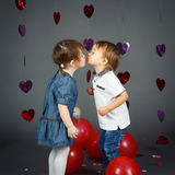 Two cute adorable baby children toddlers kissing each other in studio Royalty Free Stock Image