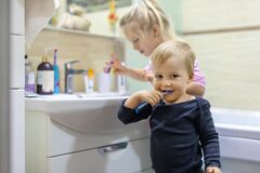 Two cute adorable blond caucasian siblings washing face and cleaning tooth with toothbrush at bathroom at home in