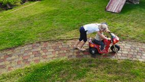 Two cute adorable blond sibings children having fun riding electric toy bike at garden path. Brother and sister enjoy. Playing and driving vehicle at house stock video footage