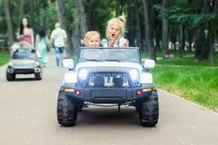 Two cute adorable blond sibings children having fun riding electric toy suv car in city park. Brother and sister enjoy playing and