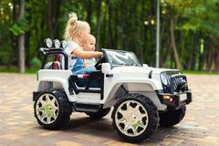 Free Two Cute Adorable Blond Sibings Children Having Fun Riding Electric Toy Suv Car In City Park. Brother And Sister Enjoy Playing And Stock Photos - 154285973