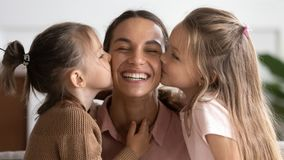 Two Cute Adorable Little Daughters Kissing Happy Mum On Cheeks Stock Images