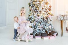 Two cute adorable little siblings brother and sister having fun playing with retro wooden wheel horse toy near christmas tree in