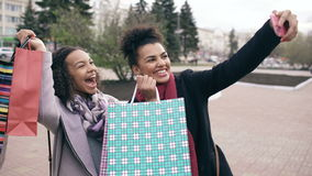 Two cute african american woman taking selfie with shopping bags and smiling. Friends have fun after visiting mall sale. stock footage