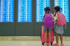 Two asian child girls with backpack checking their flight at information board in international airport terminal. Two cute asian child girls with backpack stock photography