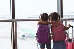 Two asian child girls with backpack looking at plane and waiting for boarding in the airport together. Two cute asian child girls with backpack looking at plane stock photography