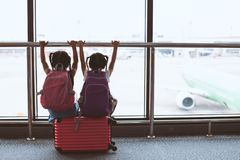 Two asian child girls with backpack looking at plane and waiting for boarding in the airport together. Two cute asian child girls with backpack looking at plane royalty free stock image