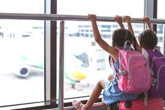 Two asian child girls with backpack looking at plane and waiting for boarding in the airport together. Two cute asian child girls with backpack looking at plane stock photos