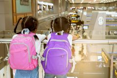 Two asian child girls with backpack waiting for boarding in the airport together. Two cute asian child girls with backpack waiting for boarding in the airport stock image