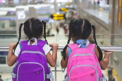 Two asian child girls with backpack waiting for boarding in the airport together stock photography