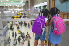 Two asian child girls with backpack waiting for boarding in the airport together. Two cute asian child girls with backpack waiting for boarding in the airport stock photos