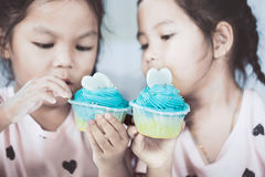 Two cute asian child girls having fun to eat blue cupcake Royalty Free Stock Images