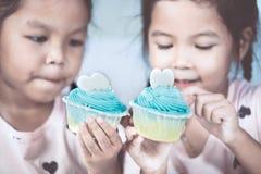 Two cute asian child girls having fun to eat blue cupcake Royalty Free Stock Photo