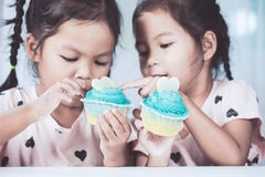 Two cute asian child girls having fun to eat blue cupcake. Together in vintage color tone stock photography