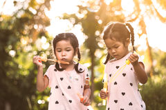 Two cute asian child girls having fun to play with bubbles Stock Image