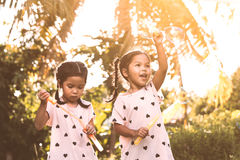 Two cute asian child girls having fun to play with bubbles Royalty Free Stock Image