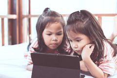 Two asian child girls having fun to play game in digital tablet Royalty Free Stock Photos