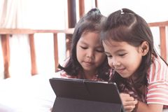 Two asian child girls having fun to play game in digital tablet Stock Photo