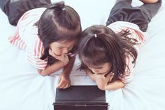 Two asian child girls having fun to play game in digital tablet Stock Images