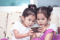 Two cute asian child girls having fun to play game in smartphone Royalty Free Stock Photography