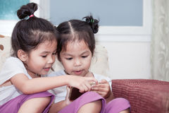 Two cute asian child girls having fun to play game in smartphone Royalty Free Stock Image