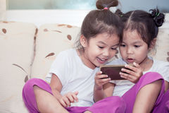 Two cute asian child girls having fun to play game in smartphone Royalty Free Stock Images