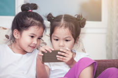 Two cute asian child girls having fun to play game in smartphone Royalty Free Stock Photo